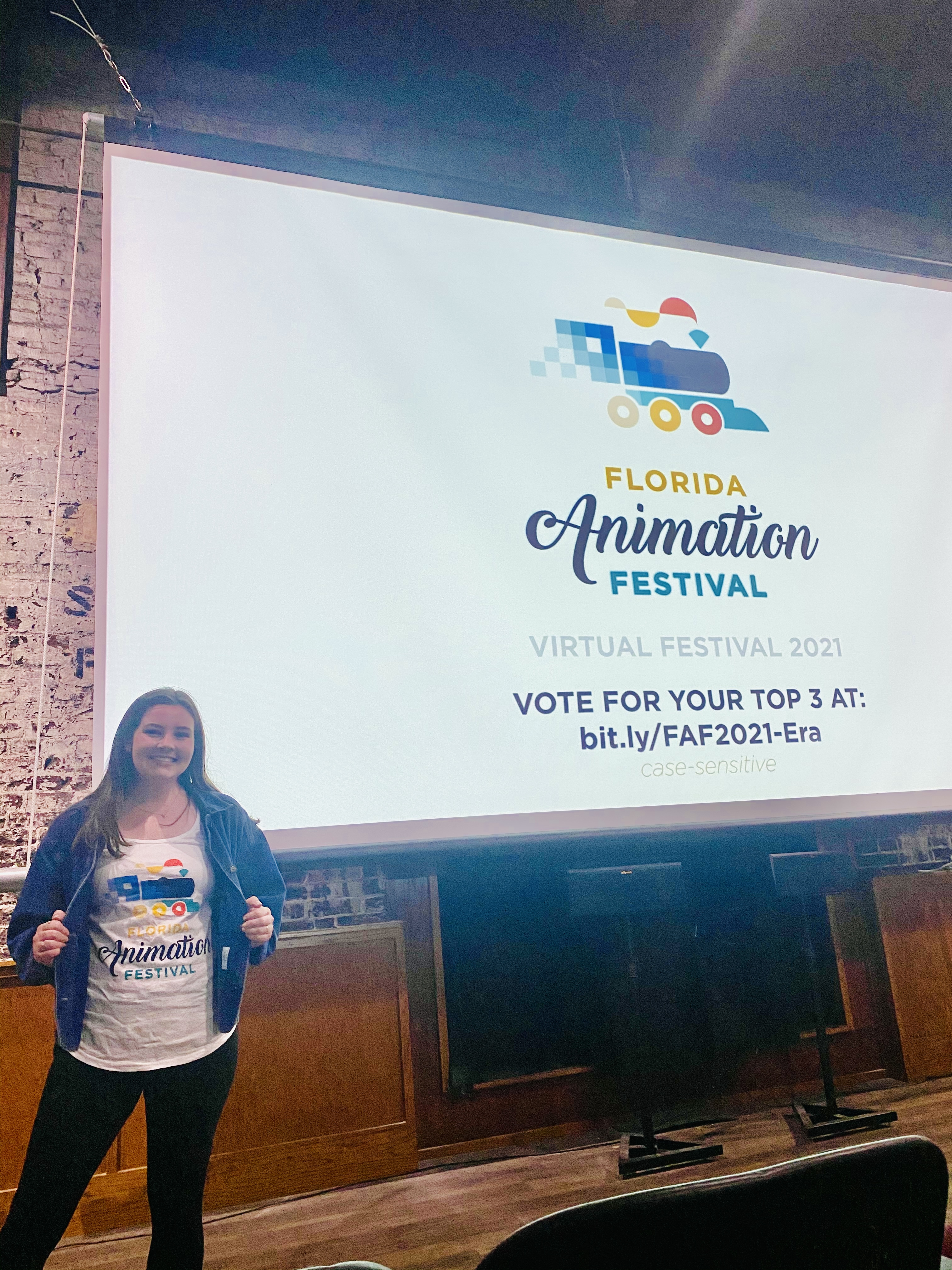 Molly Custis standing infront of a projector displaying Florida Animation Festival logo